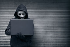 Hooded hacker with mask holding laptop while typing Stock Images