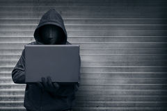 Hooded hacker with mask holding laptop while typing. Against metal roller shutter door background stock photography