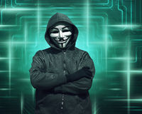 Hooded hacker with mask standing Stock Photography