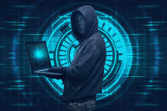 Hooded hacker with mask typing on laptop Stock Photo