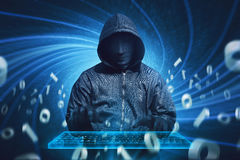 Hooded hacker with mask typing on virtual keyboard Stock Image