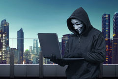 Hooded hacker with vendetta mask stealing information with lapto Royalty Free Stock Photo