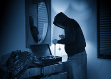 Hooded home burglar taking jewelery Stock Photos