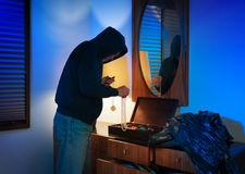 Hooded home burglar taking jewelery Royalty Free Stock Image