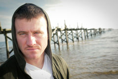 Hooded Man. A man with an intense stare wearing a hooded sweatshirt with an old pier in the background royalty free stock photos