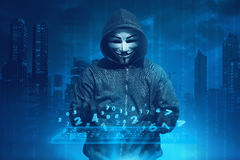 Hooded man with anonymous mask hacking system online security Royalty Free Stock Images