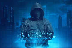 Hooded man with anonymous mask hacking system online security Royalty Free Stock Photography