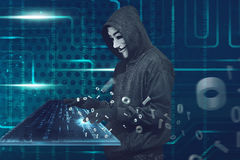 Hooded man with anonymous mask typing on virtual keyboard. Over binary code background stock photography