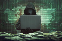 Hooded man with anonymous mask using laptop to hacking bank. System security against binary code in background royalty free stock image