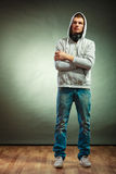 Hooded man with big headphones on neck. Music leisure youth concept. Young hooded man teen boy in full length with headphones on neck grunge background Stock Images
