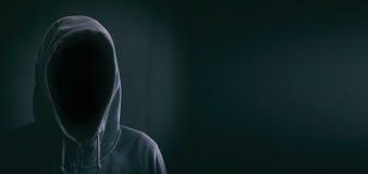 Hooded man on black background. Hooded faceless man on black background Royalty Free Stock Images