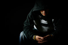 Hooded man contemplating, with mood lighting Stock Photo