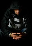 Hooded man contemplating, with mood lighting Stock Photos