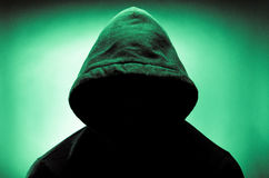 Hooded man with face in shadow. Image of a man wearing a hood with his face hidden by shadows Stock Images
