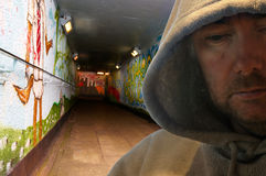 Hooded man in graffiti decorated subway. Portrait of man in hoody looking sinister - deliberately dark Stock Photography