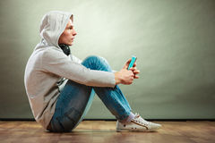 Hooded man with headphones listening music Stock Photo