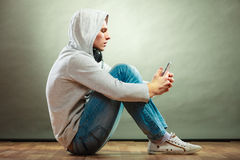 Hooded man with headphones listening music Stock Image