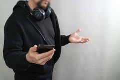 Hooded man hipster with headphones listening to music with smart. Phone mobile payment online shopping,social network,front view Royalty Free Stock Photos