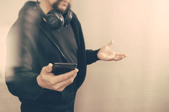 Hooded man hipster with headphones listening to music with smart. Phone mobile payment online shopping,social network,front view,filter Royalty Free Stock Photography