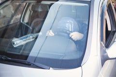 Hooded Man holding steering wheel. Driving car stock image