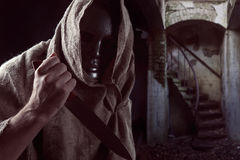 Hooded man  in iron mask  with knife Royalty Free Stock Image