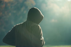 Hooded man jogging in the park in early autumn morning Stock Photos