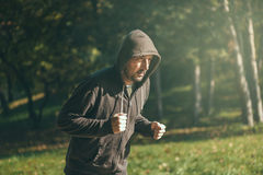 Hooded man jogging in the park in early autumn morning Stock Images