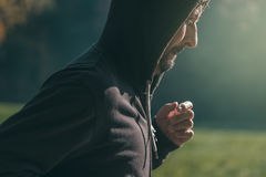 Hooded man jogging in the park in early autumn morning Royalty Free Stock Photos