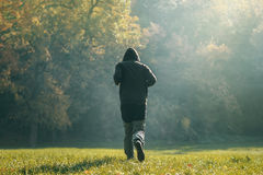 Hooded man jogging in the park in early autumn morning Royalty Free Stock Photo