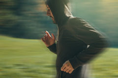 Hooded man jogging in the park in early autumn morning Royalty Free Stock Images