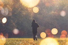 Hooded man jogging in the park. Retro toned image with selective focus and bokeh light Stock Photo