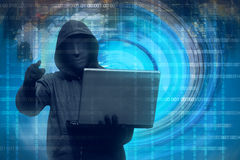 Hooded man with mask holding laptop. Against binary code in background Stock Images