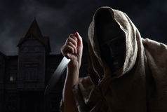 Hooded man in mask with a knife Royalty Free Stock Photo