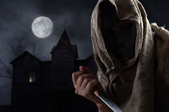 Hooded man in mask with knife Stock Photo