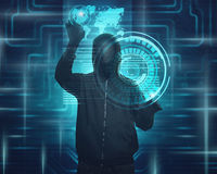 Hooded man with mask using virtual screen to hacking. Internet system security Royalty Free Stock Photo