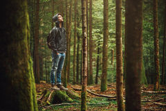 Hooded man posing in the forest. Hooded young man standing in the forest and exploring, freedom and nature concept Stock Images
