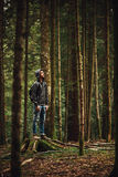 Hooded man posing in the forest. Hooded young man standing in the forest and exploring, freedom and nature concept Royalty Free Stock Image