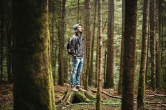 Hooded man posing in the forest. Hooded young man standing in the forest and exploring, freedom and nature concept Stock Photo