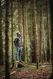 Hooded man posing in the forest. Hooded young man standing in the forest and exploring, freedom and nature concept Royalty Free Stock Photos