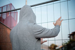 Hooded man prisoner with hand on a metal mesh Stock Photos