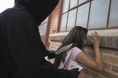 Hooded Man Robbing Young Woman With Knife Royalty Free Stock Photos