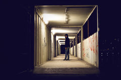 Hooded man standing in construction passage at night. royalty free stock image