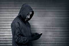 Hooded man with vendetta mask using mobile phone Royalty Free Stock Image