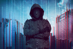 Hooded man wearing guy fawkes mask Stock Photography