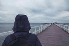 Hooded person on wooden pier walkway Stock Photo