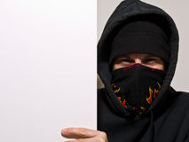 Hooded Protester Holding a Blank Sign. A hooded, masked angry man holding a blank sign Royalty Free Stock Photos