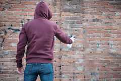 Hooded tagger writing graffiti Royalty Free Stock Photography