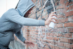 Hooded tagger writing graffiti Royalty Free Stock Photo
