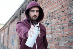 Hooded tagger writing graffiti on urban walls Stock Photography