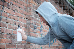 Hooded tagger writing graffiti on urban walls Stock Photography